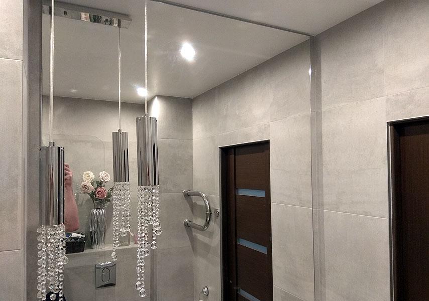 Liels vannas spogulis un stikla plauktiņi