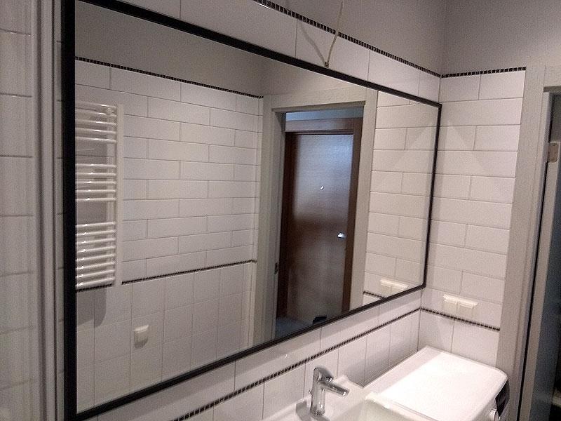 Liels spogulis melnā rāmī vannas istabai